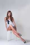 Fashion woman with long slim legs sitting on chair in studio with white paper Royalty Free Stock Photography