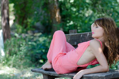 Fashion woman lying on bench , with a pink piece garment. Fashion woman lying with back on the bench wear a pink piece garment. Nice romantic outdoor photo of a royalty free stock images