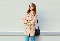 Fashion woman model with crossed arms wearing a coat black handbag over grey Stock Photography