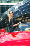 Fashion woman model in sunglasses standing next to luxury car Stock Images