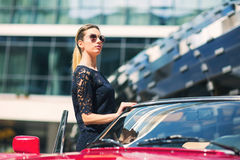 Fashion woman model in sunglasses standing next to luxury car Royalty Free Stock Image