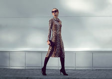 Fashion woman model wearing a leopard dress is walking. In a evening city Stock Images