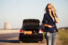 Fashion business woman next to broken car calling on cell phone Royalty Free Stock Photo