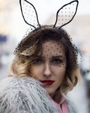 Cute blondie girl in fashion artificial fur coat and black veil with rabbit ears and red lips outside winter stock photo