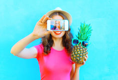 Fashion woman with pineapple taking picture self portrait on smartphone over colorful blue background screen. Closeup Stock Images