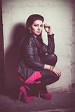 Fashion woman in pink dress and leather jacket at wall Royalty Free Stock Images