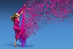 Fashion woman with pink fabric. Fashionable girl with ginger hair and bright make up posing / dancing with pink and silky fabric on blue background. Dispersion Stock Photos
