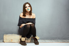 Fashion woman portrait in teenager style seating against gray w Royalty Free Stock Photography