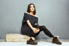 Fashion woman portrait in teenager style seating a Royalty Free Stock Photos