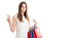 Fashion woman portrait with young shopaholic showing victory sig Stock Photos
