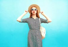 Fashion woman poses in striped dress and round straw hat. On a blue background royalty free stock photo