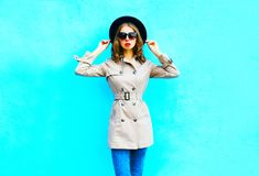 Fashion woman posing wearing a coat and black round hat. On a blue background stock photo