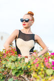 Fashion woman posing. Young cool fashion woman posing in lots of flowers Royalty Free Stock Photos
