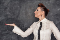 Fashion woman presenting on her empty palm. Beautiful fashion woman presenting with empty palm on the blackboard background Royalty Free Stock Images