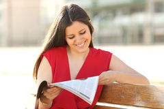 Fashion woman reading a magazine in a park Stock Images