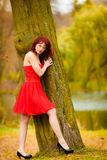 Fashion woman red dress relaxing walking in park Royalty Free Stock Photo