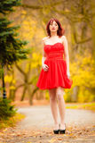 Fashion woman red dress relaxing walking in park Stock Photo