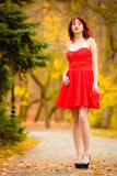 Fashion woman red dress relaxing walking in park Stock Images