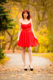 Fashion woman red dress relaxing walking in park Royalty Free Stock Images