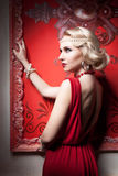Fashion woman red dress in vintage room. Professional make up and hairstyle Royalty Free Stock Image