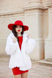 Fashion woman in red hat and dress wearing white fur coat. Elega Stock Photo