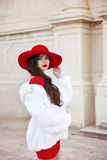 Fashion woman in red hat and dress wearing white fur coat. Elega Stock Images