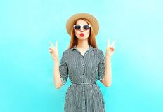 Fashion woman with red lips sends an air kiss in summer round hat. Fashion woman with red lips sends an air kiss in summer round straw hat on blue background royalty free stock image