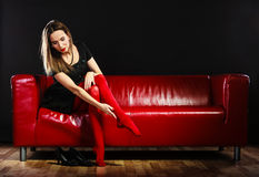 Fashion woman in red pantyhose on couch Royalty Free Stock Photos