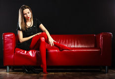 Fashion woman in red pantyhose on couch Royalty Free Stock Image