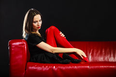 Fashion woman in red pantyhose on couch Stock Images