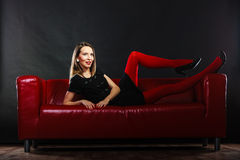 Fashion woman in red pantyhose on couch Royalty Free Stock Photography