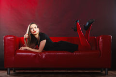 Fashion woman in red pantyhose on couch Royalty Free Stock Photo