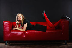 Fashion woman in red pantyhose on couch Royalty Free Stock Images