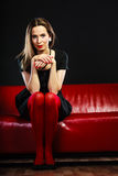 Fashion woman in red pantyhose on couch Stock Image