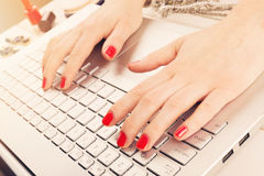 Fashion woman with red polished nails working on laptop. writing stock photography