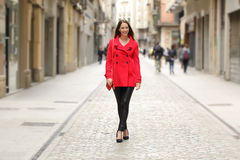 Fashion woman in red walking on a city street. Happy fashion woman in red walking on a city street in winter Stock Images