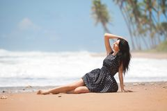 Fashion woman relaxing on the beach. Happy lifestyle. Sand, blue cloudy sky and ocean waves. Vacation at Paradise. Ocean beach. Relax, travel royalty free stock images