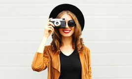 Fashion woman with retro film camera in black round hat. Brown jacket on gray wall background stock photos