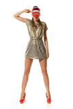 Fashion Woman Salute. Serious young woman in gold mini dress, red high heels and sun visor cap standing with legs apart and salute. Full length studio shot Royalty Free Stock Photography