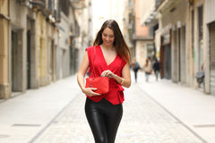 Fashion woman searching in her bag and walking. In the street stock image