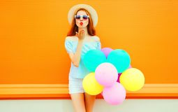 Fashion woman sends an air kiss with balloons on orange. Background Royalty Free Stock Image