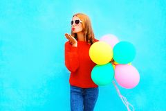 Fashion woman sends an air kiss with colorful balloons on blue. Background Stock Images