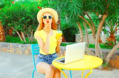 Fashion woman sends an air kiss with cup of juice and laptop Royalty Free Stock Image