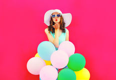 Fashion woman is sends an air kiss holds an air colorful balloons on pink background Stock Photography