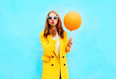 Fashion woman sends an air kiss holds balloon in a yellow coat Stock Image