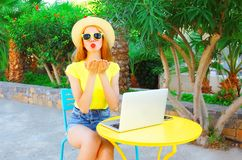 Fashion woman sends an air kiss sits at a cafe table with laptop Stock Images