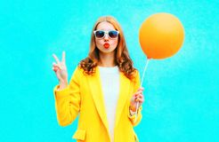 Fashion woman sends kiss holds an air balloon in yellow coat Royalty Free Stock Photography
