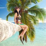 Woman siting upon palm tree on the beach Royalty Free Stock Photo