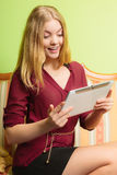 Fashion woman sitting on sofa with pc tablet. Stock Photography