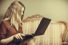 Fashion woman sitting on sofa using pc laptop Stock Images